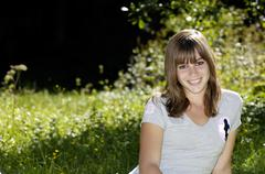 teenage girl (16-17) sitting in meadow, smiling, portrait - stock photo