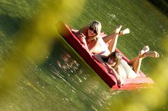 Stock Photo of two teenage girls (16-17) floating on air bed in lake, tilt view