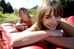 Stock Photo of young couple lying on air bed, smiling, close-up