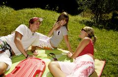 Three young adults having picnic in meadow, smiling Stock Photos