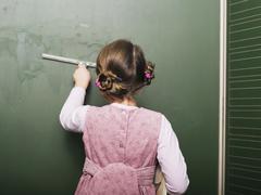 Stock Photo of girl (5-6) wiping blackboard, rear view