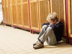 Boy (4-7) sitting in front of locker, side view Stock Photos