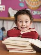 Boy (4-5) sitting at desk and leaning on stack of books, portrait, close-up Stock Photos