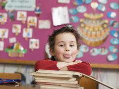 Boy sitting at school desk, leaning on stack of books Stock Photos