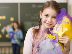 Girl (6-7) holding school cone, smiling, portrait, close-up Stock Photos