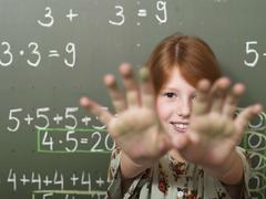 Girl (6-9) standing by black board with arms out, portrait Stock Photos