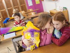 Stock Photo of girls (4-7) holding school cone whispering in classroom, tilt view