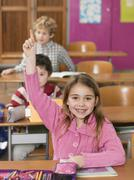 children (4-7) in classroom, girl smiling and rising hand - stock photo