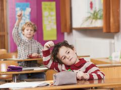 Stock Photo of children (4-7) in classroom, focus on boy with hand in hair in foreground