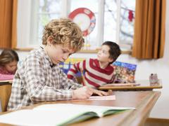 Stock Photo of children (4-7) writing exam in classroom, focus on boy