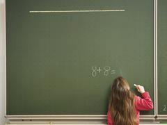 Girl standing in front of blackboard, solving arithmetic problem, rear view Stock Photos