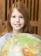 Girl (6-7) holding globe, portrait, close-up Stock Photos