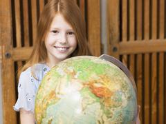 girl (4-7) holding globe, smiling, portrait - stock photo
