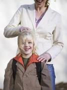 Stock Photo of boy (4-7) standing in front of mother, smiling, close-up