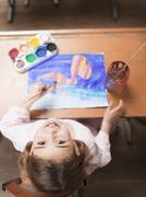 Girl painting with water colours Stock Photos