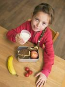 girl (4-7) holding glass of milk and lunch box by desk, elevated view - stock photo