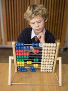 Stock Photo of boy (4-7) using abacus, close-up