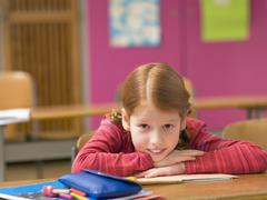 Stock Photo of girl (4-7) leaning on desk, close-up, portrait