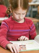 girl (4-7) reading exercise book, close-up - stock photo
