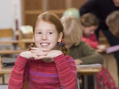 girl (4-7) in classroom, smiling, head on hands, close-up - stock photo