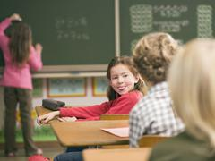 Children (4-7) in class room, focus on girl sticking out tongue Stock Photos