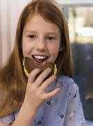 Girl (4-7) eating sandwich, close-up Stock Photos