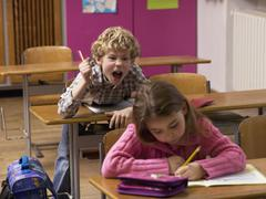 Boy (4-7) shouting behind girl in class room Stock Photos