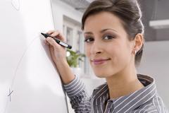 woman writing on flipchart, portrait, smiling, close-up - stock photo
