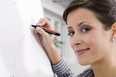 woman writing on flipchart, portrait, smiling, close-up - stock photo