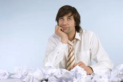 Stock Photo of man sitting at desk with crumpled papers, looking upwards