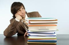 Stock Photo of businessman sitting at desk with pile of files, looking away