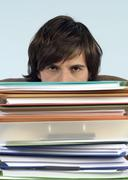 Stock Photo of man sitting on desk with stack of files, portrait, high section, close-up