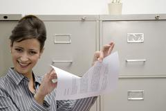 Stock Photo of woman tearing document, smiling, portrait