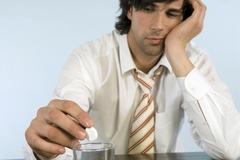 businessman holding pill, sitting on desk with glass of water, close-up - stock photo