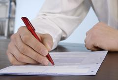 Man filling in application form, close-up Stock Photos