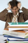 Man sitting on desk with piled files Stock Photos