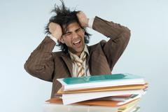 Stock Photo of man sitting at desk with piled files, shouting