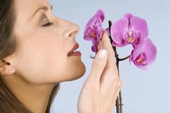 Stock Photo of young woman smelling flowers, close-up