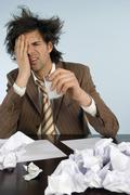 businessman sitting on desk with head in hands, papers around - stock photo