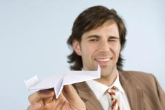 businessman holding paper plane, winking, smiling, close-up - stock photo