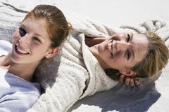 mother and daughter lying on beach, smiling, portrait, elevated view - stock photo