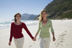mother and daughter walking on beach, hand in hand - stock photo