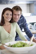 Young couple in kitchen with salad bowl Stock Photos