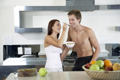 Young couple in kitchen, having breakfast Stock Photos
