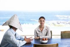 Stock Photo of couple sitting at table, man wearing shako