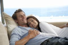 Couple relaxing on sofa Stock Photos