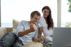 couple sitting on couch, using laptop - stock photo