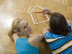 couple lying on floor, building house with pens - stock photo