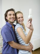 Stock Photo of couple embracing, woman holding bulb