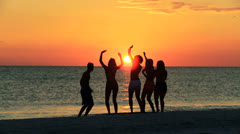 Silhouetted College Friends Laughing Dancing Beach - stock footage